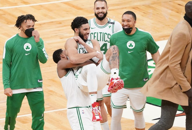 Celtics' Jayson Tatum, center, and Tristan Thompson celebrate after their victory over the San Antonio Spurs in overtime Friday night at TD Garden.