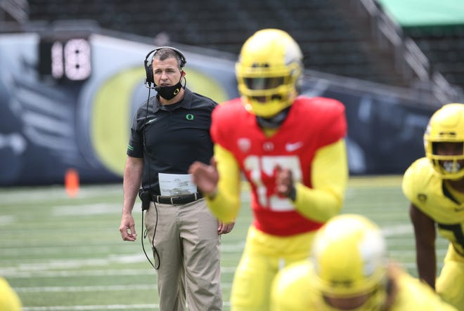 Oregon coach Mario Cristobal, left, keeps an eye on play from the backfield during the Oregon Spring Football game at Autzen Stadium.