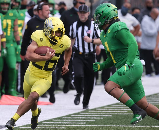 Oregon's Travis Dye, left, runs downfield under pressure from Noah Sewell during the first half of the Oregon Spring Football game at Autzen Stadium.