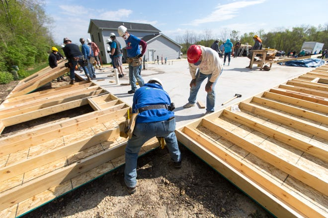 Volunteers begin to raise an exterior wall as Rockford Area Habitat for Humanity begins its construction season in the Brandon subdivision Saturday, May 1, 2021, in Rockford.