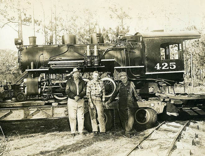 Floyd Perry, left, and his brother Fred Perry, right, stand with a man in front of Engine 425 while it sits on a trailer in this family photograph.