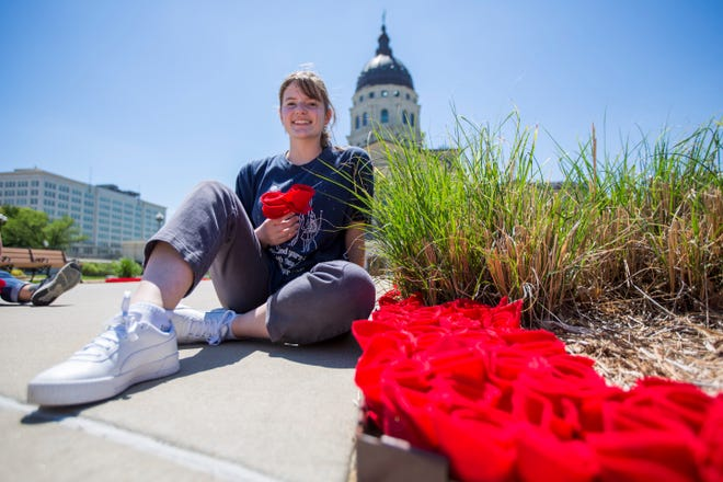 Girl Scout Anna Newcome's Gold Award project honors the 5,000 Kansans who have died from COVID-19 by planting a felt-fabric rose on the Kansas Statehouse's north lawn.
