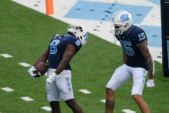 Former UNC running back Michael Carter (8) celebrates with wide receiver Beau Corrales (15) after scoring a touchdown against Virginia Tech in a 2020 game.