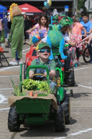 Ryker Hayden leads a group of car show entrants around the driving course, Saturday, May 1, drawn out at the Springtime in Paris Festival on the square at the Logan County Courthouse. Ryker's farm market tractor claimed the top award in the 4-8 year group. Ryker is the 4-year-old son of Brittany and Josh Robberson and Chris Hayden.
