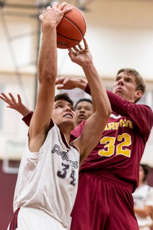Granite Hills Phillip Hammond, left, drive to the basket for a layup while guarded by Barstow's Joshua Sinclair on Friday, April 30, 2021. The Cougars won 59-52.