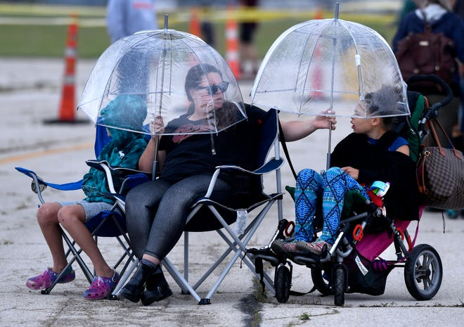 """Brooke Rice holds an umbrella over her daughter Saida, 8, as she and her 11 year-old son Brody watch AirFest 2021 at Abilene Regional Airport on Saturday. While there was some rain at the air show, it never was heavy. """"I didn't see enough planes for me to get under a wing,"""" Brooke said."""