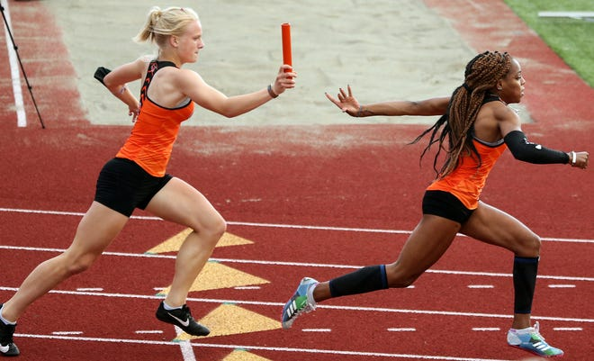 Central Kitsap's Savannah Fourier hands the baton off to Kymeal Gaulden during the 4x100m relay for the Virtual State Meet at Central Kitsap High School on Friday, April 30, 2021.