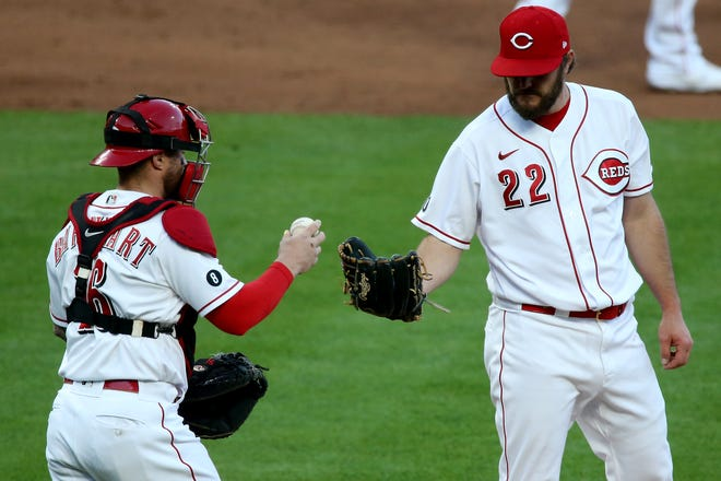 Cincinnati Reds catcher Tucker Barnhart (16) visits Cincinnati Reds starting pitcher Wade Miley (22) at the mound in the third inning of a baseball game against the Chicago Cubs, Friday, April 30, 2021, at Great American Ball Park in Cincinnati.