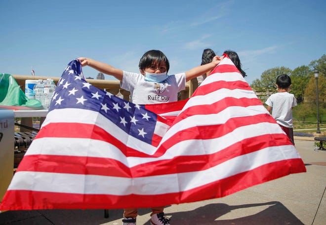 Yirmeyahu Rodriquez, 5, of Des Moines, waves a U.S. flag at the Iowa Capitol grounds during a march and rally for immigration reform on Saturday, May 1, 2021. The march began at La Placita on East Grand and ended in a rally at the Capitol Building.