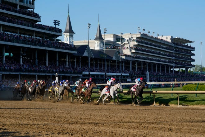 Medina Spirit, right, with John Velazquez aboard, leads the field around the first turn on the way to winning the 147th running of the Kentucky Derby.
