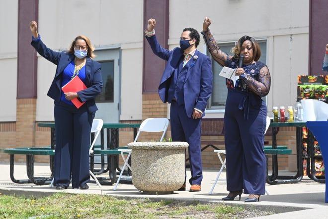 Gwendolyn Thomas, kiri, Pendeta Damon Dillard, dan Alana Dillard mengangkat tangan mereka dalam persatuan selama Pawai Kesadaran Pencegahan Pelecehan Anak dan Kesehatan Mental pada hari Sabtu, 1 Mei 2021.