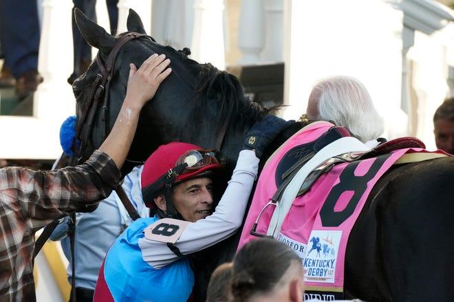 Jockey John Velazquez memeluk Medina Spirit di lingkaran pemenang setelah memenangkan perlombaan ke-147 di Kentucky Derby pada hari Sabtu di Churchill Downs di Louisville, Kentucky.