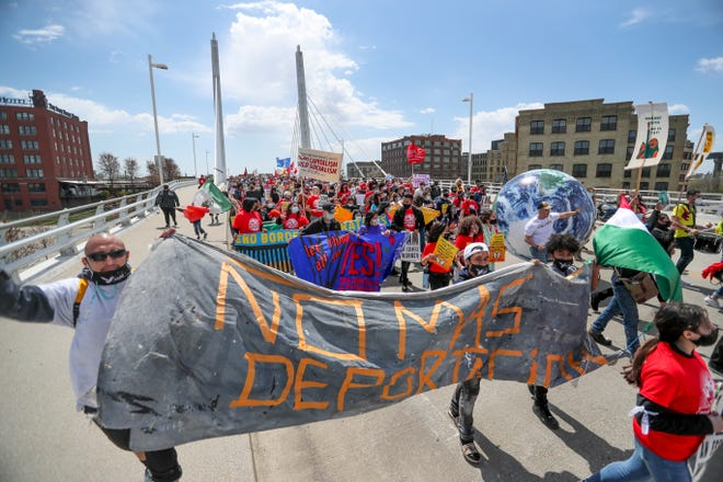 Protesters march over the 6th Street South Bascule Bridge during a rally hosted by Voces de la Frontera Action and VDLF Essential Workers Rights Network on Saturday, May 1, 2021, in Milwaukee. This group marched from 6th Street and ended at the Federal Building in downtown Milwaukee.