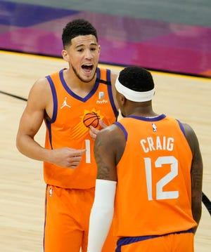 Apr 30, 2021; Phoenix, Arizona, USA; Phoenix Suns guard Devin Booker (1) talks to forward Torrey Craig (12) against the Utah Jazz in the first half at Phoenix Suns Arena. Mandatory Credit: Rob Schumacher-Arizona Republic