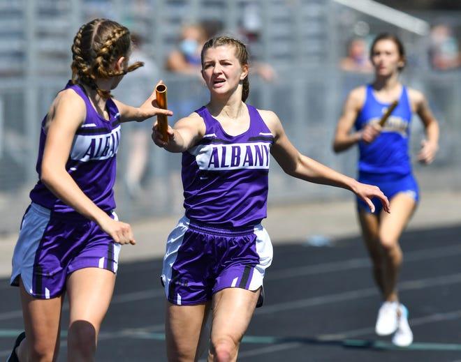 Albany's Olivia Goebel hands the baton to Megan Koglin  during the 4x400 meter relay Saturday, May 1, 2021, during the Sauk Rapids Mega Meet.