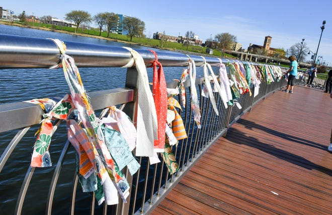 Strips of cloth are tied to a railing on the shore of Lake George before the start of a COVID-19 memorial event Saturday, May 1, 2021, at Lake George in St. Cloud.