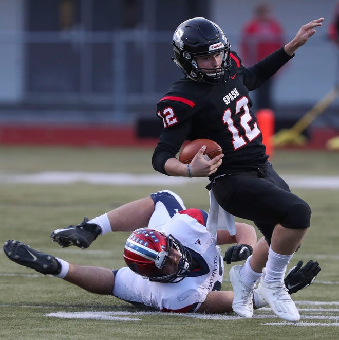 SPASH's Riley Warzynski (12) is tripped up by Appleton East's Alex Moz during a game April 30 at Goerke Field in Stevens Point.