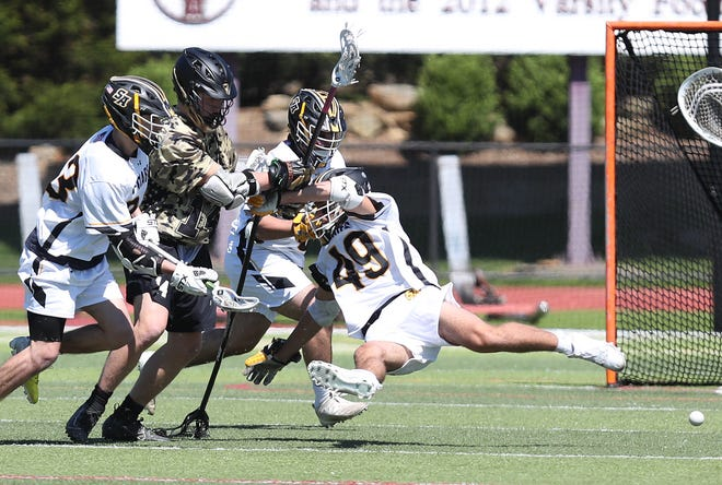Iona's Scott Mackie (14) gets hit by a host of Saint Anthony's defenders as they battle for a ground ball during lacrosse action at Iona Prep in New Rochelle on Saturday. Saint Anthony's won the game 14-8.