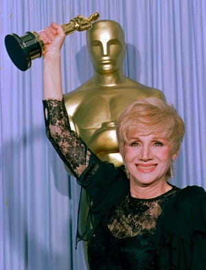 """FILE - In this April 11, 1988 file photo, Olympia Dukakis holds her Oscar  at the Shrine Auditorium in Los Angles after being honored at the 60th Academy Awards as best supporting actress for her role in """"Moonstrck."""" Olympia Dukakis, the veteran stage and screen actress whose flair for maternal roles helped her win an Oscar as Cher's mother in the romantic comedy """"Moonstruck,"""" has died. She was 89. (AP Photo/Lennox Mcleondon, File) ORG XMIT: NY950"""