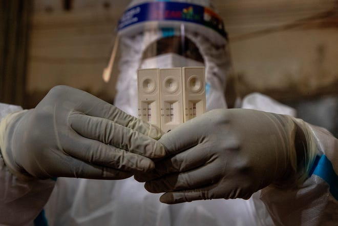 A health worker in PPE displays test kits of COVID-19 positive persons after testing election officials and polling agents on the eve of state elections results in Gauhati, India, Saturday, May 1, 2021.