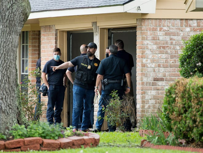 Law enforcement officials investigate the site of a human smuggling case, where more than 90 undocumented immigrants were found inside a home on the 12200 block of Chessington Drive on Friday, April 30, 2021, in Houston. A Houston Police officials said the case will be handled by federal authorities.