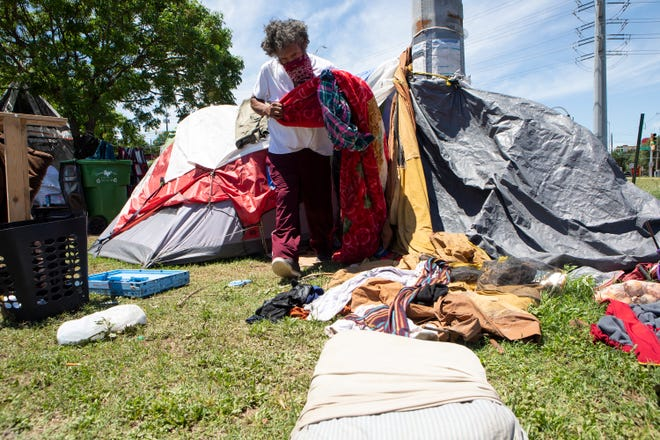 John N., who did not want to give his full last name, removes rain-soaked clothes and bedding from his tent on Sunday. He has been homeless for the past six months and living off Riverside Drive.