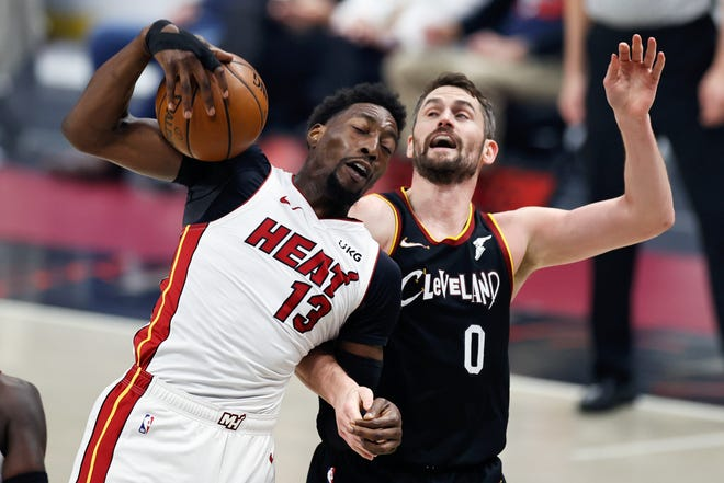 Miami Heat's Bam Adebayo (13) grabs a rebound in front of Cavaliers forward Kevin Love (0) during the first half of their game Saturday night in Cleveland. [Ron Schwane/Associated Press]