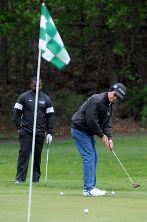 Frank Golembiewski, representing a team from the University of Mount Union, follows his putt as Darnell Tucker looks on during the Alliance Chamber of Commerce Women's Division Golf Outing at Sleepy Hollow Country Club on Friday. A total of 23 teams entered the event.
