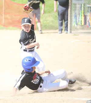 Tint Shop's Tallin Kempf beats the throw home while Fayette pitcher Sawyer Asbury attempts to make the tag in the first inning Saturday in Cal Ripken Minor at the Cooper County Baseball Association ballfield.