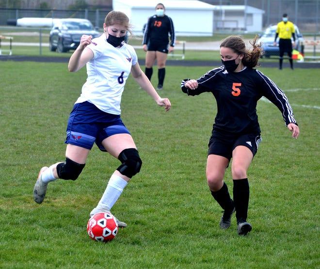 Cheboygan junior midfielder Elizabeth Markham (5) and Boyne City senior Ally Herrick battle for the ball during the first half of a varsity girls soccer matchup in Cheboygan on Saturday.