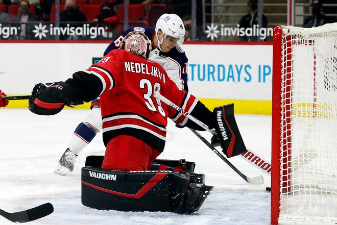 Columbus Blue Jackets' Max Domi (16) slips the puck past Carolina Hurricanes goaltender Alex Nedeljkovic (39) for a goal during the first period of an NHL hockey game in Raleigh, N.C., Saturday, May 1, 2021. (AP Photo/Karl B DeBlaker)