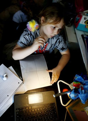 Lily Jucha, 8, does her distanced learning in her bedroom. Her mother, Sara Jucha, stays home to help her children manage remote schooling.