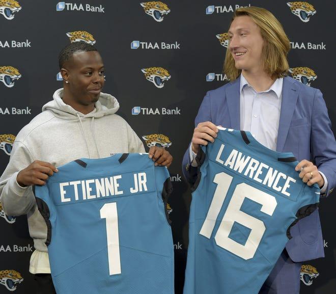 Clemson running back Travis Etienne (L) and quarterback Trevor Lawrence (R), the top two draft picks for the Jaguars, received the best grades on Gene Frenette's draft report card.