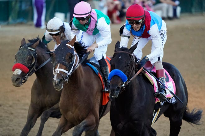 John Velazquez, riding Medina Spirit, right, leads Florent Geroux on Mandaloun and Flavien Prat on Hot Rod Charlie to win the 147th running of the Kentucky Derby at Churchill Downs on Saturday.