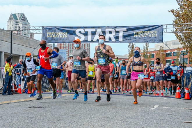 Waves of runners begin the staggered start of the Providence Marathon in downtown Providence on Sunday.