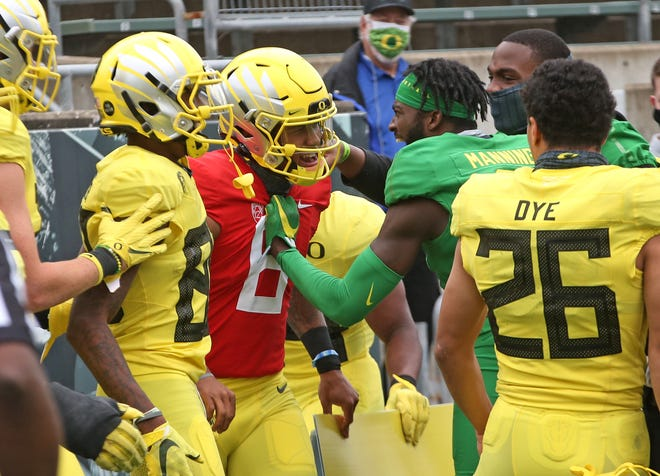 Oregon quarterback Robby Ashford, center, celebrates with teammates after scoring a two-point conversion to win the game for the Yellow team during Saturday's Oregon spring football game at Autzen Stadium.