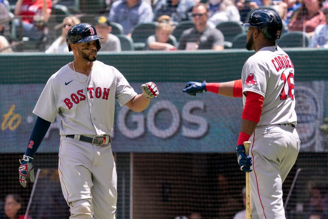 Boston Red Sox's Xander Bogaerts, left, is congratulated by Franchy Cordero (16) after scoring on a groundout by Hunter Renfroe during the first inning of a baseball game against the Texas Rangers Sunday, May 2, 2021, in Arlington, Texas.
