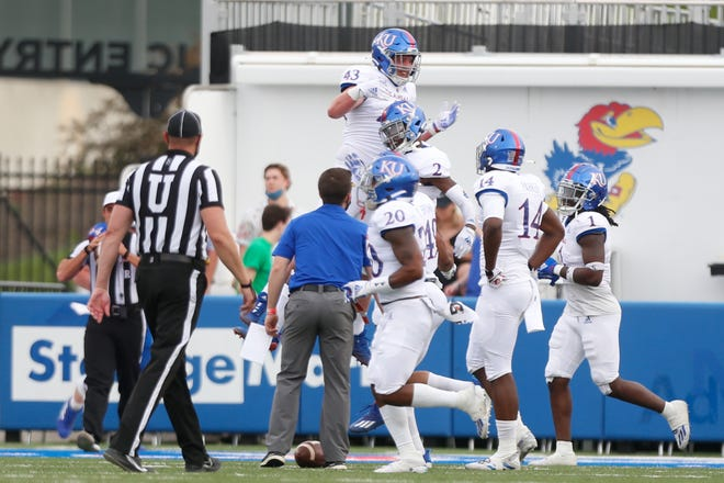 Kansas defensive players on the White team celebrate a pick-six by freshman cornerback Jacobee Bryant (2) in the first quarter of Saturday's spring game scrimmage at David Booth Kansas Memorial Stadium in Lawrence.