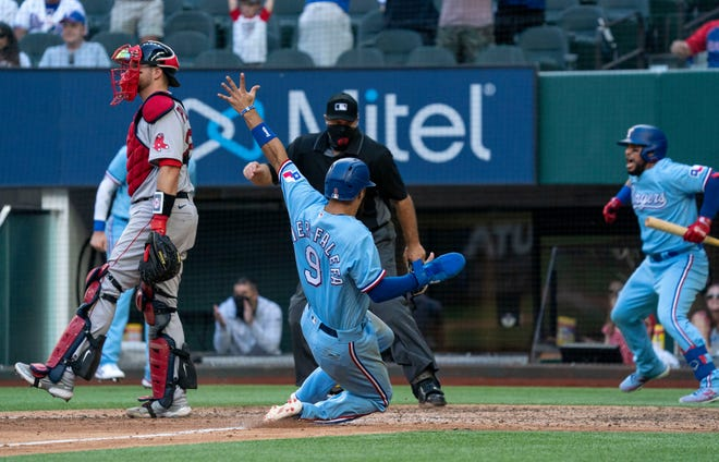 Isiah Kiner-Falefa scores on a go-ahead RBI-single by teammate Brock Holt as home plate umpire Brian O'Nora and Boston catcher Kevin Plawecki look on while Rangers' Jose Trevino, right, celebrates during the eighth inning of Sunday's game.