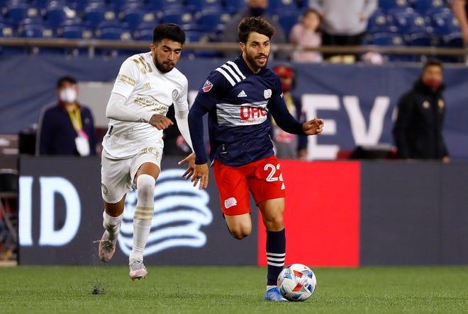 Revolution midfielder Carles Gil, right. goes past Atlanta United midfielder Marcelino Moreno during the second half Saturday night at Gillette Stadium.