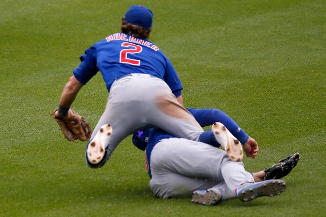 Chicago Cubs shortstop Nico Hoerner (2) and center fielder Ian Happ (8) collide while tracking a fly ball in the eighth inning of the MLB National League game between the Cincinnati Reds and the Chicago Cubs at Great American Ball Park on Sunday, May 2, 2021.