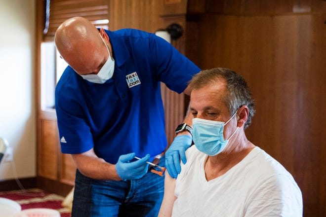 VaxiTaxi volunteer Dustin Villhauer administers a dose of the Pfizer COVID-19 vaccine Sunday at the Islamic and Cultural Center in Granger. Organizers of the clinic were hoping to get 300 Bosnian residents of the town their first of two shots.