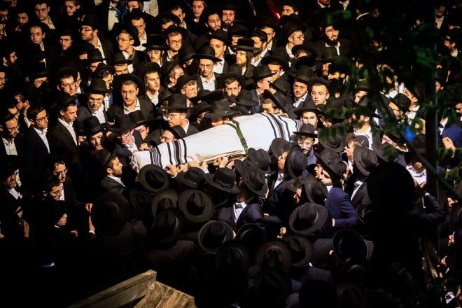 Pria Ultra-Ortodoks Yahudi membawa tubuh Yossi Kohn, 21, dari Cleveland, Ohio, yang meninggal selama perayaan Lag BaOmer di Mt. Meron di Israel utara, pada pemakamannya di Yerusalem, Minggu. Itu adalah salah satu bencana sipil paling mematikan di negara itu.