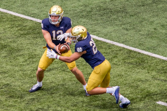 Notre Dame quarterback Tyler Buchner (12) hands off to running back Chris Tyree (25) during the Blue-Gold spring NCAA college football game on Saturday, May 1, 2021, in South Bend, Ind. (AP Photo/Robert Franklin)