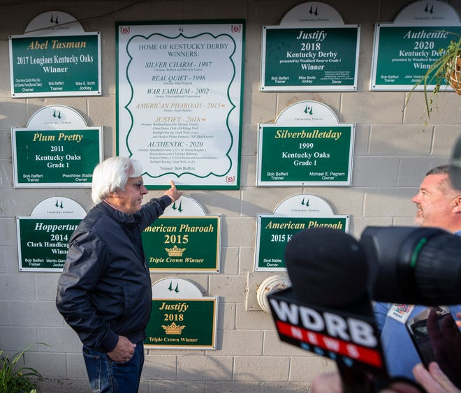 Bob Baffert points to a sign outside his barn listing all of his Kentucky Derby winners on the day after his seventh victory in the race with Medina Spirit. May 2, 2021