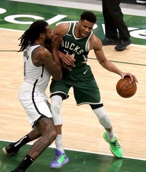 Bucks forward Giannis Antetokounmpo works the ball against Nets center DeAndre Jordan just inside the paint during the second quarter.