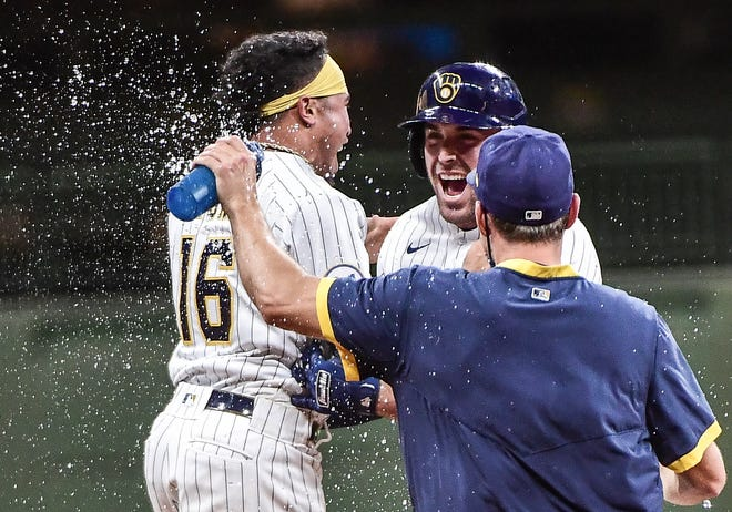 Kolton Wong and other Brewers players converge on Travis Shaw after his winning two-out RBI single against the Dodgers in the bottom of the 11th inninng.