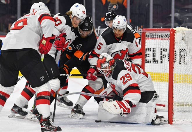May 1, 2021; Philadelphia, Pa. -- New Jersey Devils goaltender Mackenzie Blackwood (29) covers the puck with help from center Jesper Boqvist (90) and defenseman Connor Carrick (5) against Philadelphia Flyers center Sean Couturier (14) during the first period at Wells Fargo Center.