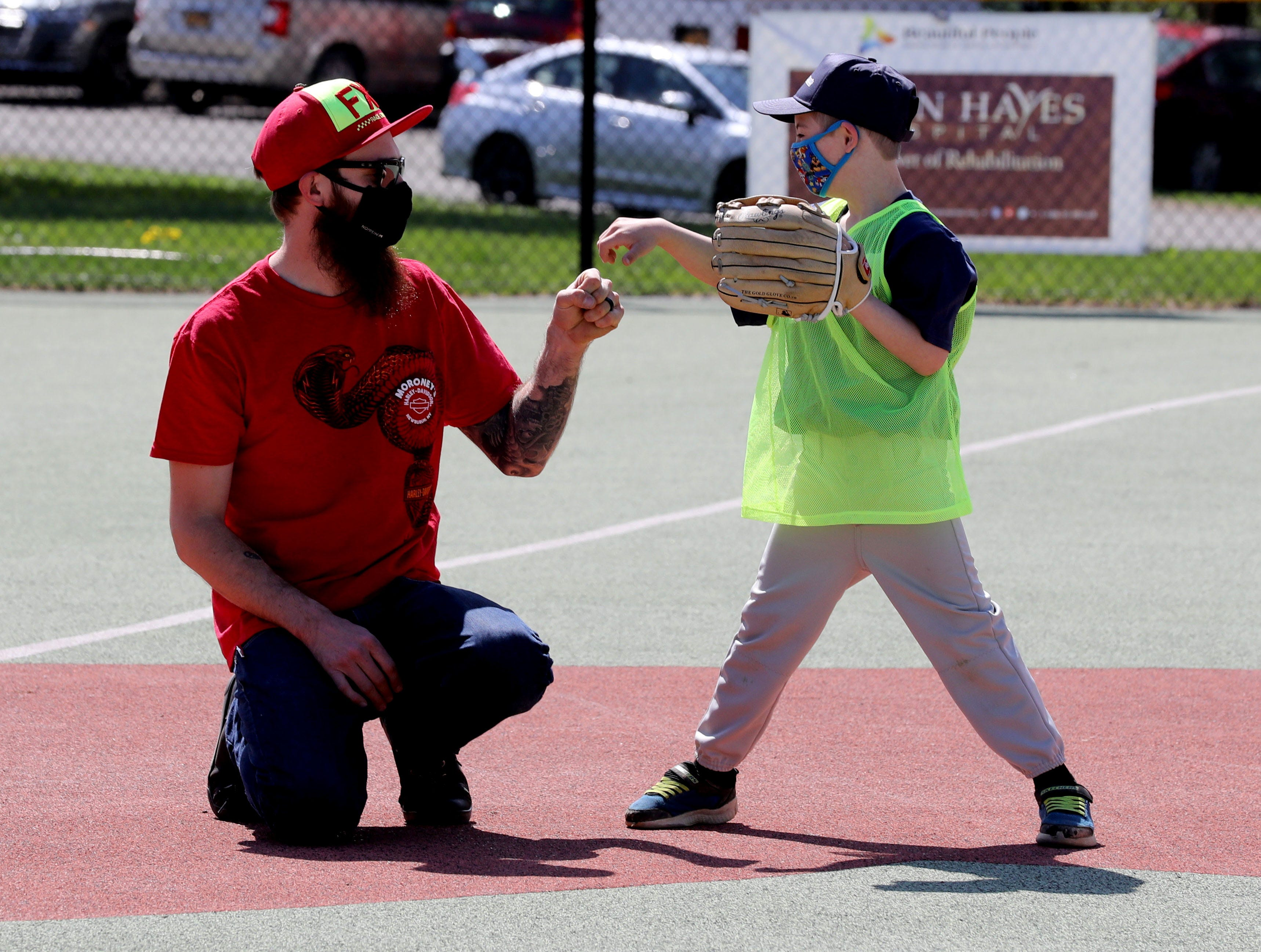 Michael Delaney, 8, of Warwick, N.Y. fist bumps his father Mike as he plays baseball during opening day for Beautiful People Baseball in Warwick, N.Y. May 2, 2021. The baseball program is one of the sports offered by Beautiful People, which provided adaptive sports for children with disabilities.