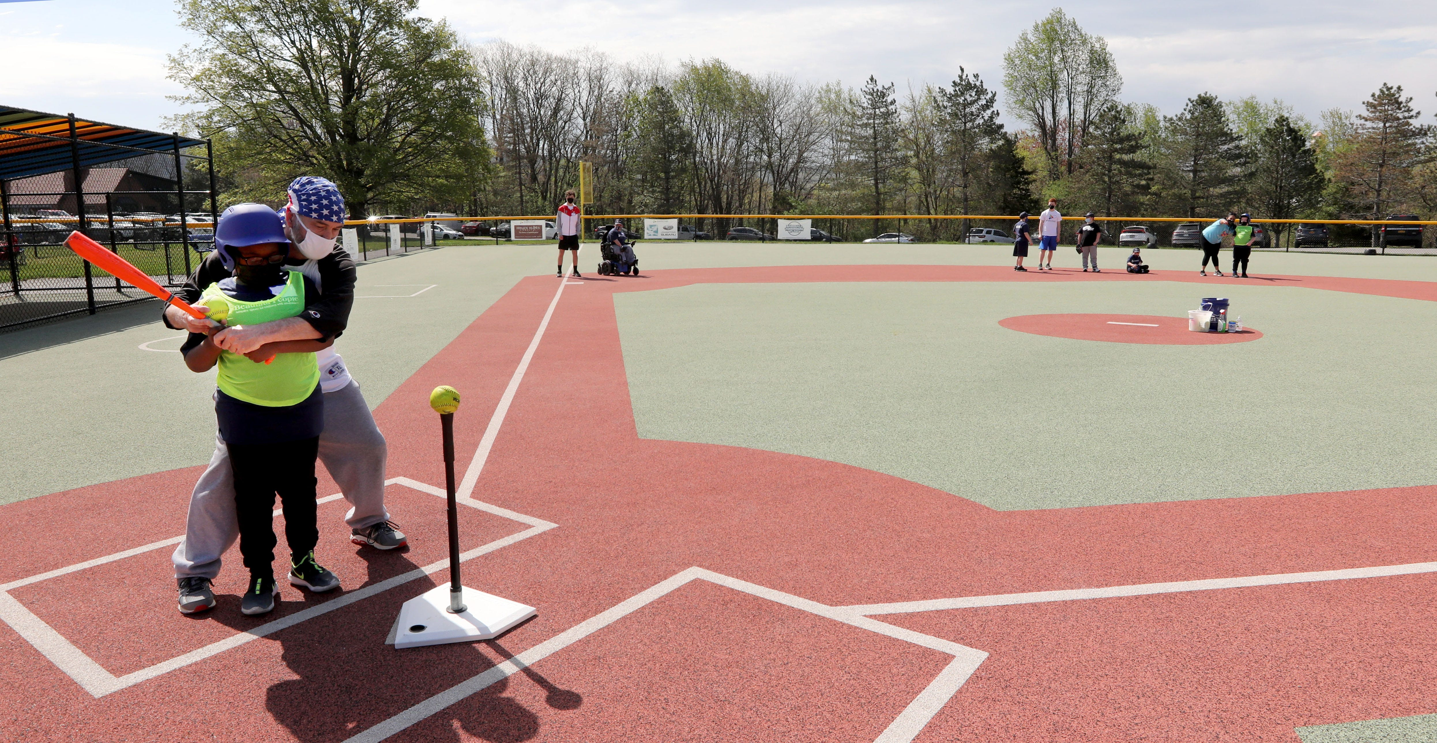 Ryan Howard 8, of Middletown, N.Y. is assisted by Bob McClorey of Warwick, N.Y. as he hits during opening day for Beautiful People Baseball in Warwick, May 2, 2021. The baseball program is one of the sports offered by Beautiful People, which provided adaptive sports for children with disabilities.